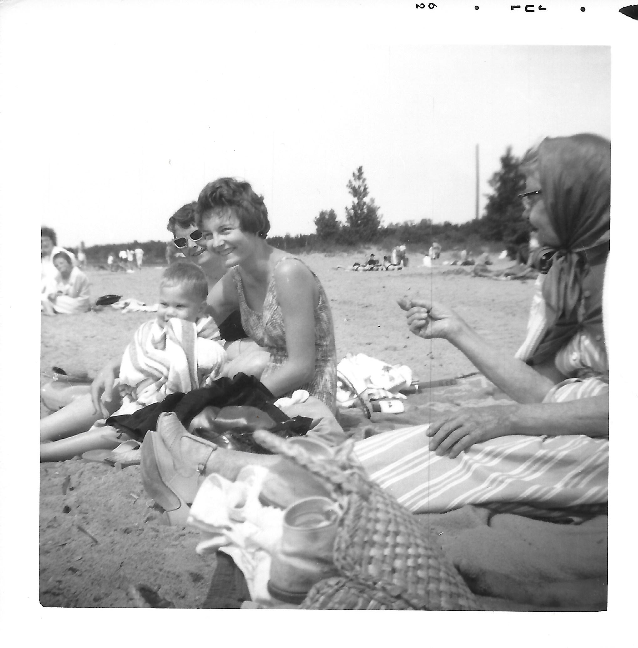 Ruth Nichols, Sherry Nichols, and Emma Ehmann at the beach.  Christopher Berg is in Sherry's lap.